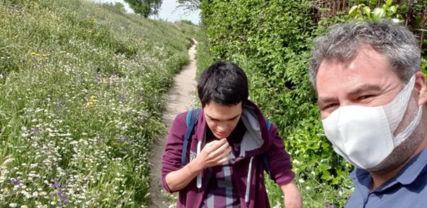 Fotografía de dos personas paseando por el campo, una de ellas lleva mascarilla y está acompañando a otra que no puede llevar la mascarilla